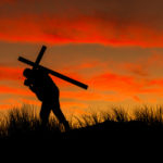 Man carrying a cross on his back at sunrise.